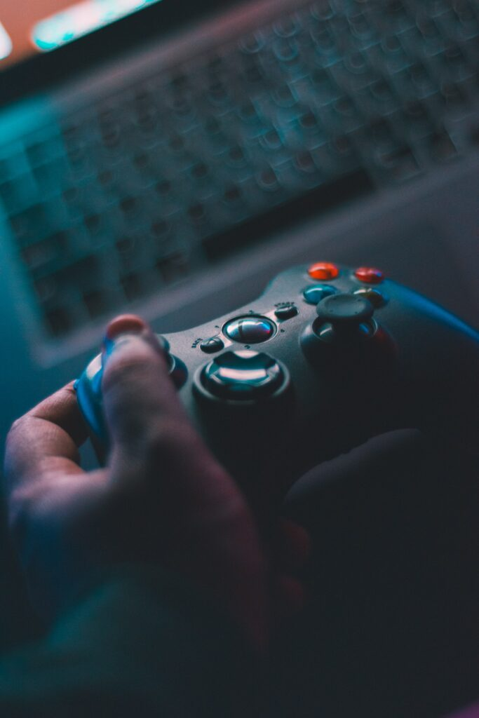 A left hand holding a joystick with a laptop in the background