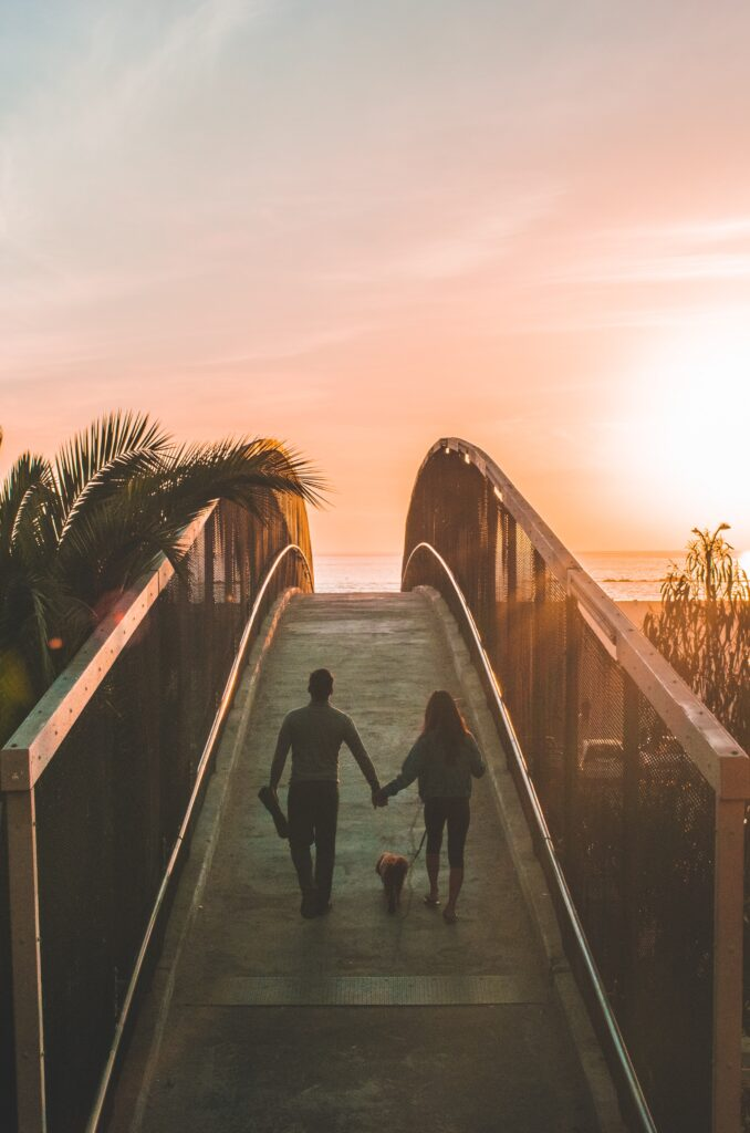 A man and a women walking a dog over a bridge with the sea and the sun in the end